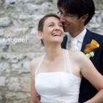 photo de couple qui sourit devant un mur en pierre