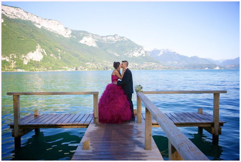 photo de couple bord de lac annecy mariés robe rose gilet rose bouquet mariée